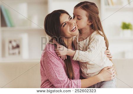 Cute Daughter Kissed Young Mother. Family Concept. Parents And Kids. Beautiful Young Mother. Little