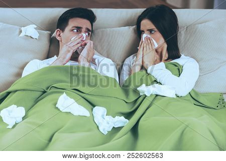 Sick Couple Blowing Noses. Napkins On Sofa. Treatment At Home. Diseas And Illnesses. Sick Man And Wo