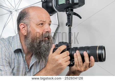 An image of a bearded senior photographer at work