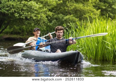 Kayaking On The River. Two Friends In A Boat Sailing Along The River. Rowers With Oars In A Canoe. R