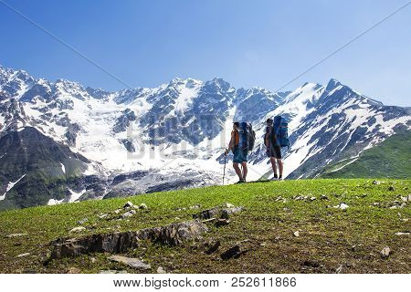 Hikers Look At Mountain Range On A Sunny Summer Day. Tourists In The Highlands. Hiking In The Mounta