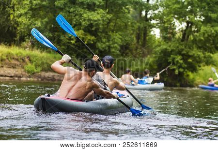 Kayaking On The River. Young Men Are Rafting Along A Wild River In A Kayak. Rowers With Oars In The