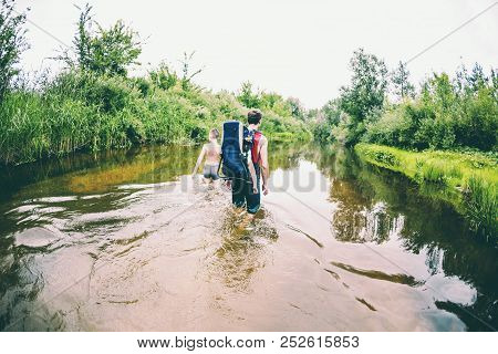A Man With A Children Crosses The River. The Father Carries The Son In A Backpack. Rescue From Flood