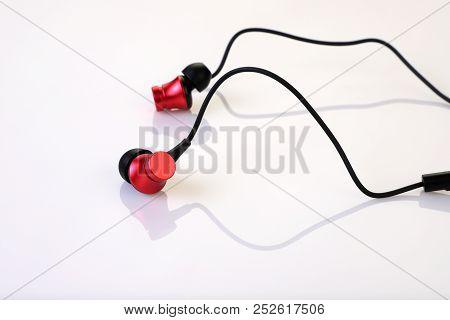 Stylish Red Earphones On White Reflective Background