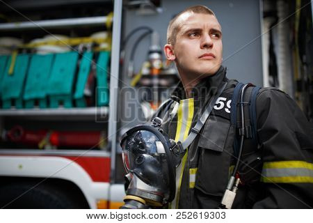 Photo of firefighter standing near fire truck with fire hose