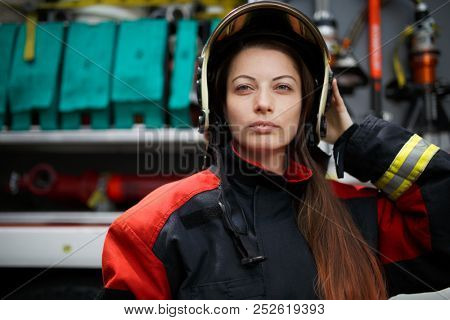 Photo of young fire woman with long hair in helmet looking into camera next to fire engine