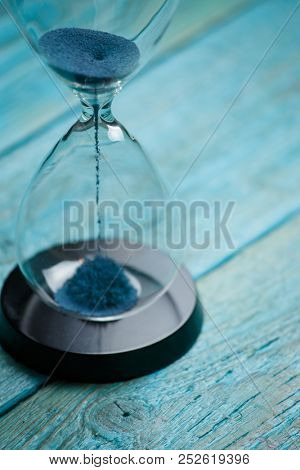 Photo of hourglass with blue sand