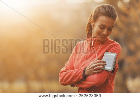 Girl Choose Music For Running. In Autumn Park. Young Beautiful Woman Doing Sports. Listening Music C