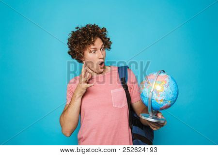 Portrait of caucasian genius guy with curly hair wearing backpack holding earth globe isolated over blue background poster
