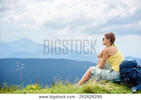Back View Of Attractive Woman Tourist Sitting And Resting On Grassy Hill With Backpack. Female Backp