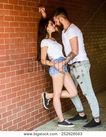 Desire and temptation. Couple find place to be alone. Couple enjoy intimacy moment without witnesses. Girl and hipster strong desire feeling. Couple in love full of desire brick wall background poster