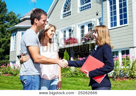Happy family with agent realtor near new house.