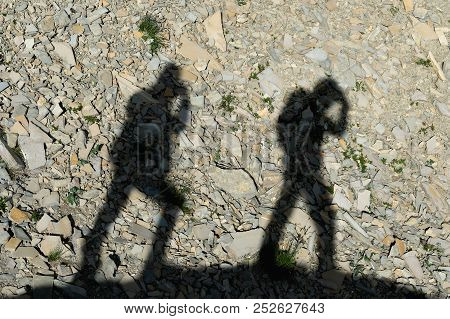 Two Shadows Of Photographers On The Earth Going Uphill. Silhouettes Of Two People Walking Uphill