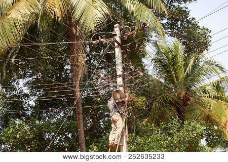 Electrician Repairing A Fault On An Electric Pole. Electrician On The Stairs At The Electric Pole Re