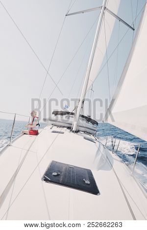 Young blonde woman wearing red life jacket and shorts sitting on deck under sails and enjoying sailing trip on boat during Greece vacation - yachting holidays concept