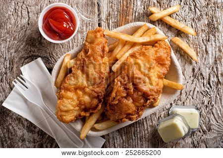 Delicious Fish And Chips In A Take Out Container With Ketchup, Tartar Sauce, Paper Napkins And A Pla