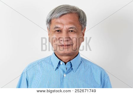 Portrait Of Attractive Senior Asian Man Smiling And Looking At Camera In Studio With White Isolated