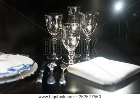 Glasses, Forks, Knives, Napkins On Dark Black Table