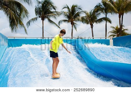 Teenager Surfing In Beach Wave Simulator Attraction In Water Amusement Park Of Tropical Resort. Teen
