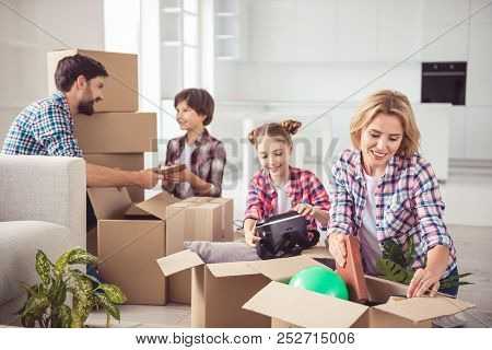 Young Happy Smiling Family Four Persons Unpacking Carton Boxes With Stuff In Light Kitchen Living Ro