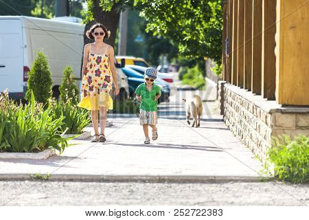 Mom And Child Are Walking Along The City Street.