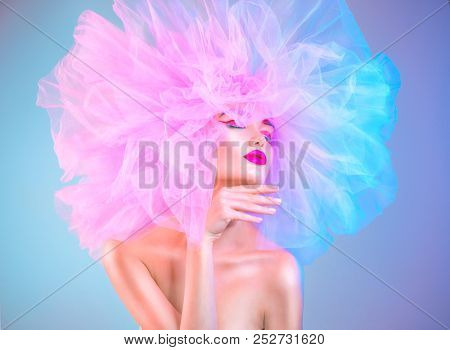 High Fashion model woman in colorful bright neon lights posing, portrait of beautiful sexy girl with trendy make-up and colourful hairdo. Art design, colorful make up. Vivid makeup.