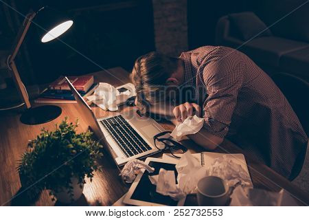 Portrait Of Exhausted, Attractive, Bored, Tired Man In Shirt Putting Face On Arms Sitting At Desk In