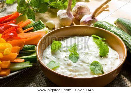 A bowl of tzatziki dip and fresh cut vegetable sticks next to it
