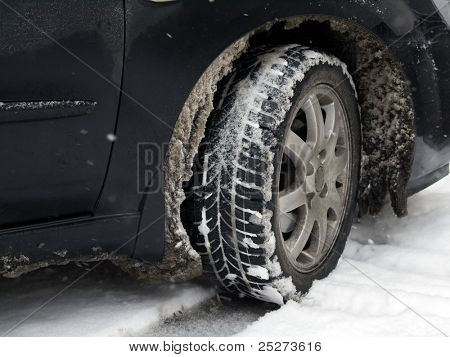 Dirty car tire with snow