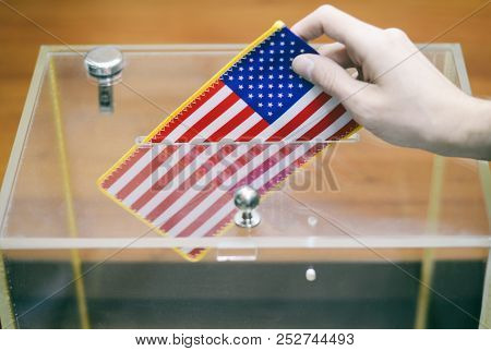 Man Inserting Flag Of United States Of America Into Ballot Box, Voting And Elections In United State