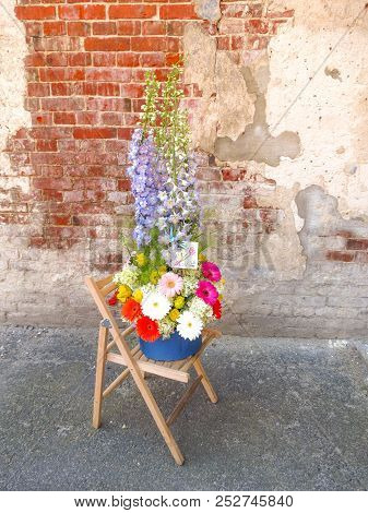 Stylish, Fashionable Floral Bouquet In A Box On A Chair Against A Brick Wall Grunge Background. The