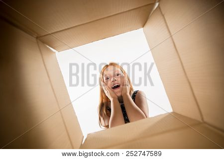 The Surprised Girl Unpacking, Opening Carton Box And Looking Inside. The Package, Delivery, Surprise