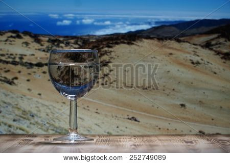 A glass glass glass with clean water stands on a wooden table against a mountain landscape.