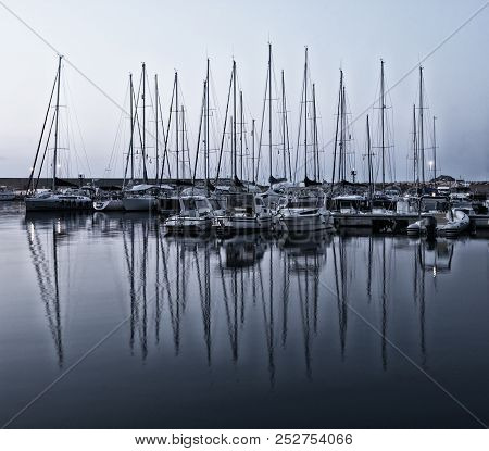 Yacht Pier In Late Evening Light. Sunset.view To Pier. Yachts With Reflections. Silhouette Of Yachts