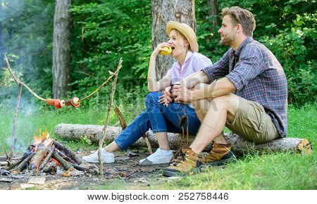Couple Romantic Date Near Bonfire In Forest. Couple Relaxing Sit On Log Having Snacks. Pleasant Picn