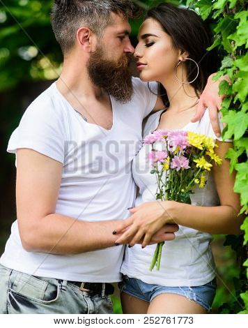 Man bearded hipster hugs gorgeous girlfriend. Couple in love going to kiss. Pleasant romantic kiss. Couple love romantic date nature park background. Love relations romantic feelings. Gentle kiss poster