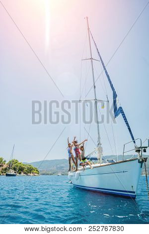 Happy Family - Mother With Two Kids Having Fun And Jumping In Sea Of Sailing Yacht On Summer Cruise.