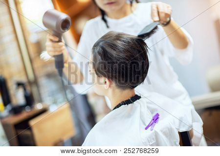 Beauty, hairstyle, treatment, hair care concept, young woman and hairdresser cutting hair at hairdressing salon. Hairdresser cuts beautiful girl's hair. Hairstylist serving client at barber shop.