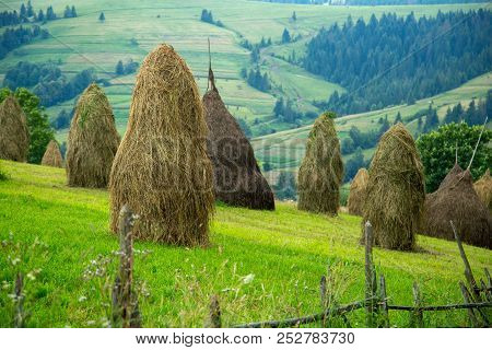 Stack Of Hay On A Mountain Meadow On A Hillside.