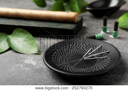 Plate With Needles For Acupuncture On Dark Table