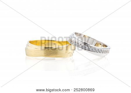 Pair Of Golden Mens Ring And Silver Womens Wedding Ring With Diamonds Isolated On White Background