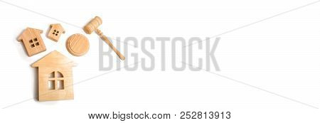 Three Wooden Houses And A Hammer Of The Judge On A White Background. Court Cases On Property And Rea