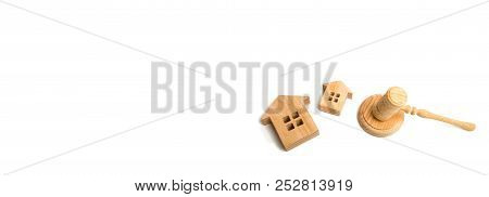 Two Wooden Houses And A Hammer Of The Judge On A White Background. Concept Of Court Cases On Propert
