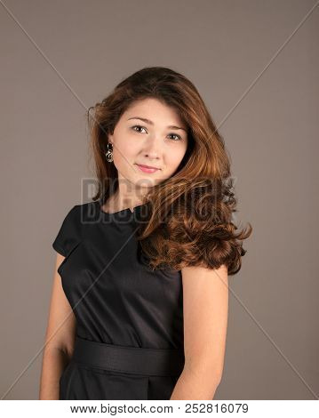 Portrait Of A Fashionable Elegant Girl In A Black Dress On A Dark Background. Evening Image. Evening