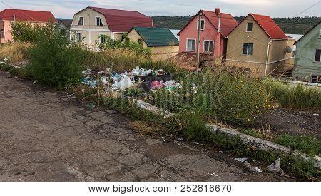 Незаконная свалка на обочине дороги. Куча пластиковых мусора и других мусора на стороне дороги, проб