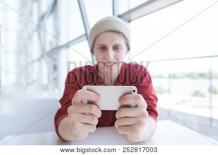 Smiling Young Man Sits In A Cafe And Uses A Smearphone. Attractive Man Watches A Video On A Smartpho