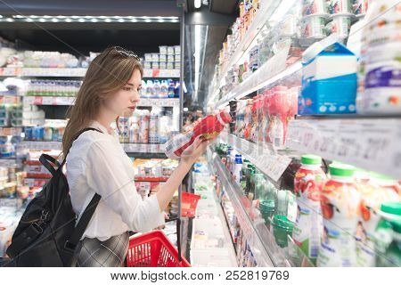 Stylish Attractive Woman Is Standing By The Refrigerator With Dairy Products, Holds Yogurt In His Ha
