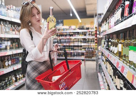Stylish Woman Is Standing In A Supermarket In The Alcohol Department And Looking At The Bottle Of Wi