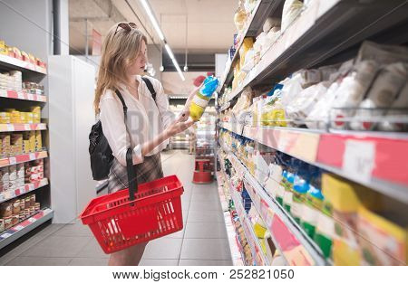 Stylish Young Girl Standing In A Grocery Supermarket In Her Arms And Reading A Label. Female Buyer S