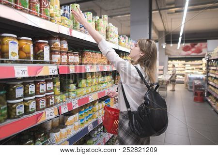 Stylish Girl With A Red Basket Takes Canned Vegetables From The Supermarket Shelf. Woman Buys Canned